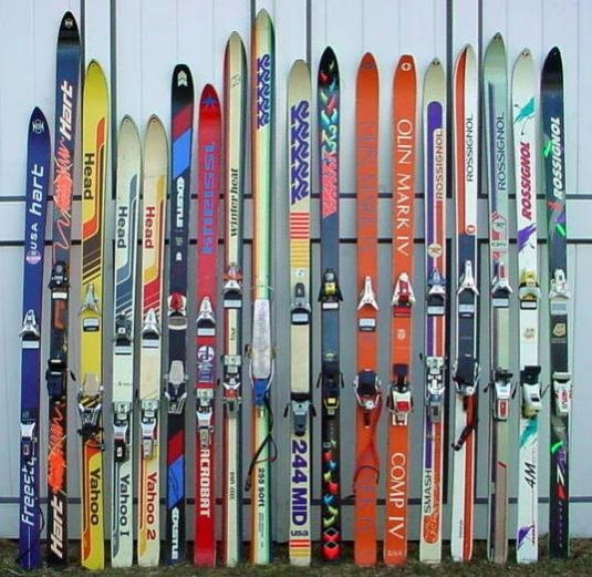 A collection of old skis against a wall